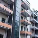 Balkonanlagen an Mehrfamilienhaus mit Balkotec-Balkonplattenbelag und Geländer mit Füllung aus Verkleidungsplatten.