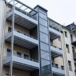 Balkonanlagen an Mehrfamilienhaus mit Balkotec-Balkonplattenbelag<br> und Geländer mit Füllung aus Verkleidungsplatten.