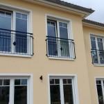 Balkongeländer und französische Fenstergitter an einem Einfamilienhaus
