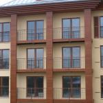 Freitragende Balkonanlage an Hotel in Hamburg mit Geländer. <br>Unterkonstruktion komplett mit Holz verkleidet