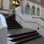 Edelstahlhandlauf parallel zur geschwungenen<br> Betonwand am Eingang der Ludwig Richter Grundschule
