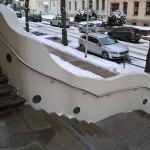 Edelstahlhandlauf parallel zur geschwungenen Betonwand am Eingang der Ludwig Richter Grundschule