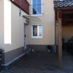 Freitragende Glasscheibe als Vordach an einem Reihenhaus