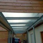 Carport mit Holzverkleidung und teilweiser Überdachung mit Glas